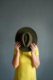 Ella cubre su cara con un sombrero Foto vertical fotografía de archivo libre de regalías