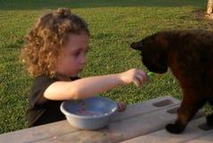 Ella die de kat voedt Stock Foto