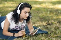Ella escucha la música y la charla vía su teléfono móvil con su franco Imagen de archivo