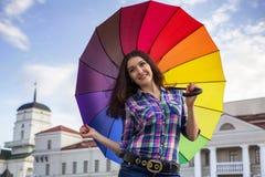 Ella está sosteniendo un paraguas colorido Foto de archivo