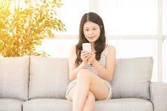 Ella está utilizando un smartphone y mandar un SMS Fotografía de archivo libre de regalías