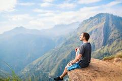Ella gap views. Young man enjoying breathtaking views over mountains and tea plantations from Little Adams peak in Ella Sri Lanka Royalty Free Stock Image