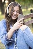 Ella goza mientras que escucha la música y la charla con sus amigos v Imagen de archivo libre de regalías