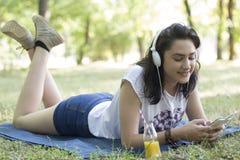 Ella goza mientras que miente en la hierba y escucha la música Fotos de archivo