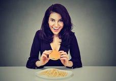 Ella le gustan los alimentos de preparación rápida Mujer joven feliz que come el cheeseburger y las patatas fritas fotos de archivo libres de regalías