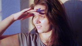 Ella puso su mano a ella los ojos del sol brillante, de que miraría en la distancia, 4k almacen de video