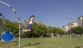 Ella que salta como saltamontes en el patio foto de archivo