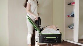 Ella recoge una maleta con cosas el vacaciones metrajes