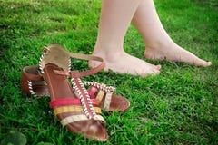 Ella sacó sus sandalias y paseos descalzo en la hierba foto de archivo