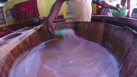 ELLA, SRI LANKA - EM MARÇO DE 2014: Equipe o vinho de derramamento do coco, igualmente chamado Araca, na garrafa pronta para que  filme