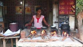 ELLA, SRI LANKA - EM MARÇO DE 2014: Mulher local que cozinha o alimento no lado da rua O alimento da rua é muito comum, saboroso  filme