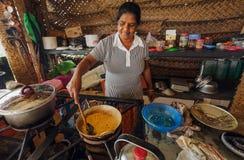 Elderly woman cooking dal food from lentils or beans on rural kitchen. ELLA, SRI LANKA - JAN 2, 2017: Elderly woman cooking dal food from lentils or beans on Stock Photos