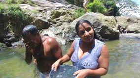 ELLA, SRI LANKA - MÄRZ 2014: Die Frau, die im Fluss steht, gießt Wasser vom Eimer auf  stock footage