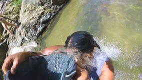ELLA, SRI LANKA - MÄRZ 2014: Die Frau, die im Fluss steht, gießt Wasser vom Eimer auf  stock video