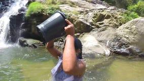 ELLA, SRI LANKA - MÄRZ 2014: Frau gießt Wasser auf vom Eimer während Stände im Fluss stock footage