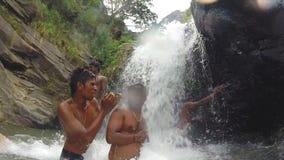ELLA, SRI LANKA - MÄRZ 2014: Lokale Leute, die das Süßwasser von Ravana-Wasserfall genießen stock video footage