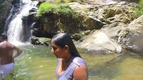 ELLA, SRI LANKA - MÄRZ 2014: Zeitlupe der Frau stehend im strömenden Wasser des Flusses vom Eimer auf  stock video footage