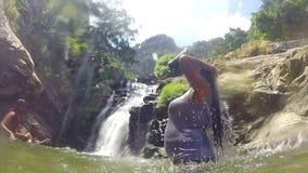 ELLA, SRI LANKA - MÄRZ 2014: Zeitlupe der Frau stehend im strömenden Wasser des Flusses vom Eimer auf  stock video