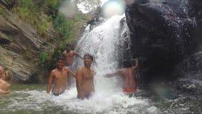 ELLA, SRI LANKA - MÄRZ 2014: Zeitlupe von den entspannten Leuten, die im Fluss vor Wasserfall stehen stock footage