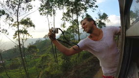 ELLA, SRI LANKA - MARCH 2014: Tourists enjoying train ride through Sri Lankan tea plantation foothills stock footage