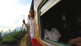 ELLA, SRI LANKA - MARCH 2014: Tourists enjoying train ride through Sri Lankan tea plantation foothills stock video