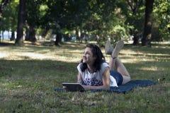 Ella utiliza una tableta y se relaja en naturaleza Fotografía de archivo
