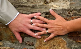 Ella y él y sus manos con los anillos de bodas Foto de archivo