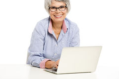 Ellderly woman working with a laptop Stock Photo
