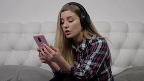 Elle écoute la musique par des écouteurs clips vidéos