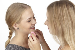 Elle aide son amie avec des quelques cosmétiques Images libres de droits