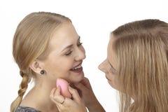 Elle aide son amie avec des quelques cosmétiques Photos stock