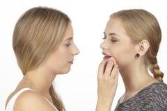 Elle aide son amie avec des quelques cosmétiques Photographie stock libre de droits