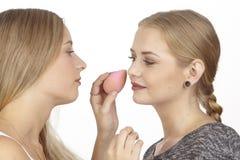 Elle aide son amie avec des quelques cosmétiques Image libre de droits