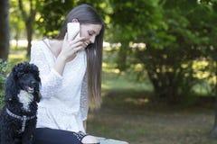 Elle apprécie avec son chien en parc et parle sur un mobile Photographie stock libre de droits