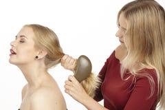 Elle balaye son amie les cheveux Image stock