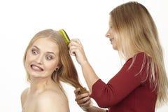 Elle balaye son amie les cheveux - ils piaulent Photographie stock libre de droits