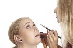 Elle emploie la poudre sur le visage de son amie Photographie stock