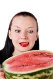 Elle lèche ses languettes regardant la pastèque Image libre de droits
