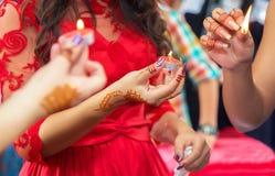 Elle tient la bougie en sa partie de henné de main Des mains et les doigts sont dessinés au henné Main femelle avec le tatouage d image libre de droits