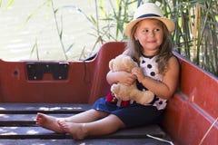 Elle tient son jouet préféré de peluche et apprécie le beau su ensoleillé Images libres de droits