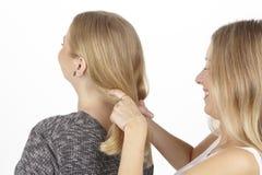 Elle tresse son amie un tresse dans les cheveux Photo libre de droits