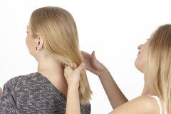 Elle tresse son amie un tresse dans les cheveux Photo stock