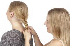 Elle tresse son amie un tresse dans les cheveux Images libres de droits