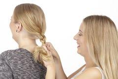 Elle tresse son amie un tresse dans les cheveux Images stock
