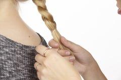 Elle tresse son amie un tresse dans les cheveux Image stock