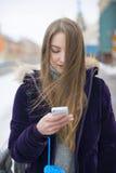Elle utilise le téléphone sur la rue Photographie stock libre de droits