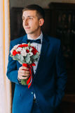 Ellegant bridegroom in blue suit with bow-tie holding a bouquet forward to meeting his bride Stock Photos