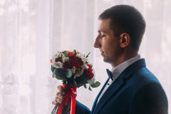 Ellegant bridegroom with bow-tie holding a bouquet. White curtains are in the background Stock Images