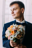 Ellegant dressed romantic groom holding a wedding bouquet of white and pale orange roses in hands standing near the Royalty Free Stock Photos