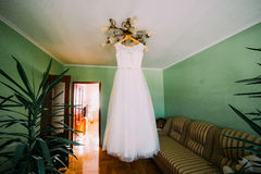 Ellegant white wedding dress hanging on lustre at hotel room decorated with exotic plants Royalty Free Stock Image